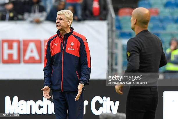 Arsenal's French head coach Arsene Wenger and Manchester City's Spanish head coach Pep Guardiola react during the friendly football match between...