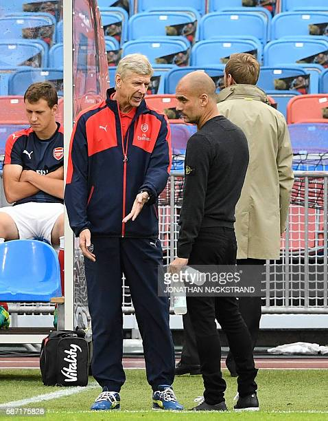 Arsenal's French head coach Arsene Wenger speak to Manchester City's Spanish head coach Pep Guardiola prior to the friendly football match between...