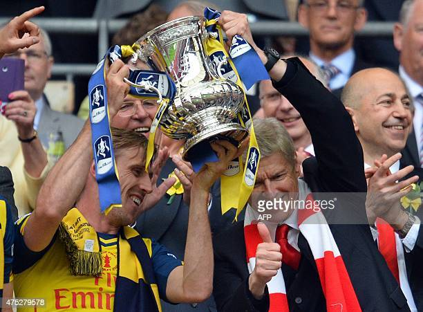 Arsenal's French manager Arsene Wenger and Arsenal's Spanish defender Nacho Monreal hold up the trophy after winning the FA Cup final football match...
