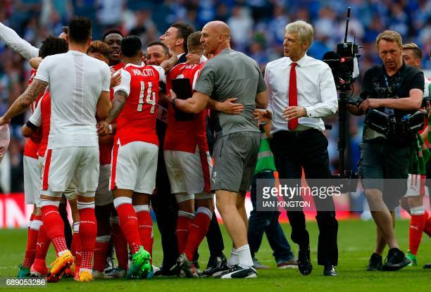 Arsenal's French manager Arsene Wenger and his assistant Steve Bould celebrate with the players on the pitch after the English FA Cup final football...