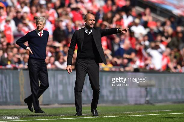 Arsenal's French manager Arsene Wenger and Manchester City's Spanish manager Pep Guardiola gesture on the touchline during the FA Cup semifinal...
