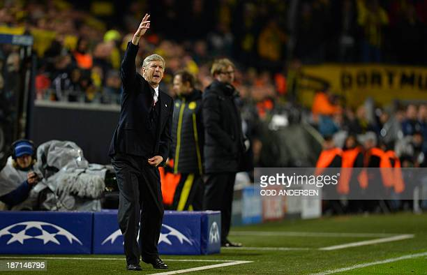 Arsenal's French manager Arsene Wenger gestures as he and Dortmund's head coach Juergen Klopp follow the action during the UEFA Champions League...