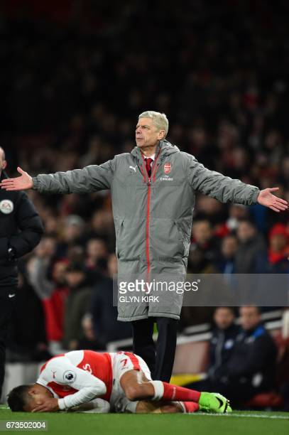 Arsenal's French manager Arsene Wenger gestures on the touchline as Arsenal's Chilean striker Alexis Sanchez lies injured during the English Premier...