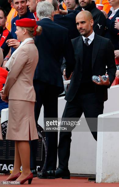 Arsenal's French manager Arsene Wenger greets Manchester City's Spanish manager Pep Guardiola ahead of during the English Premier League football...