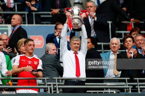 Arsenal's French manager Arsene Wenger lifts the FA Cup trophy after their win over Chelsea in the English FA Cup final football match between...