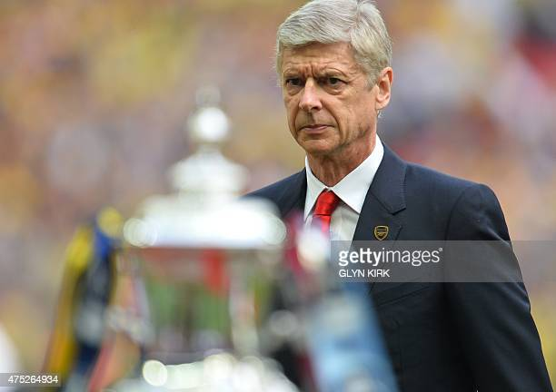 Arsenal's French manager Arsene Wenger looks at the FA cup trophy before the FA Cup final football match between Aston Villa and Arsenal at Wembley...