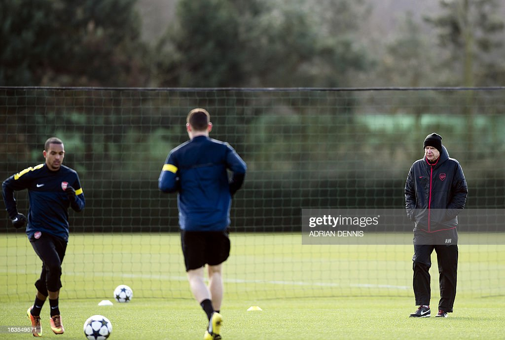 Arsenal's French manager Arsene Wenger (R) looks on as Theo Walcott (L) and Thomas Vermaelen (C) warm up during a training session at the club's complex in London Colney on March 12, 2013 ahead of the team's last 16 UEFA Champions League football match against Bayern Munich in Germany on March 13.