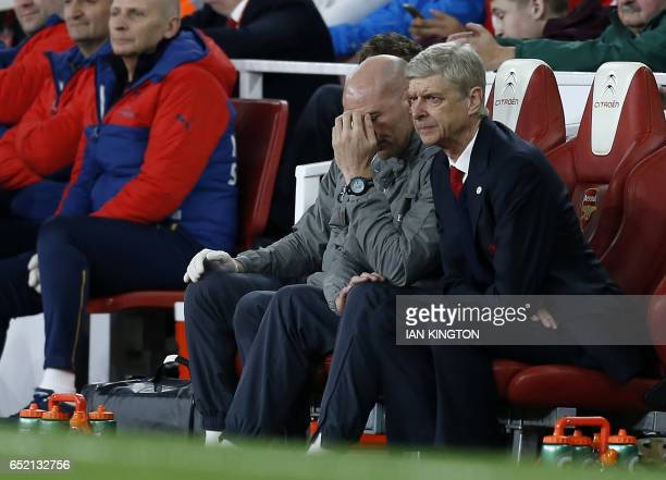 Arsenal's French manager Arsene Wenger looks on from the dugout during the English FA cup quarter final football match between Arsenal and Lincoln...