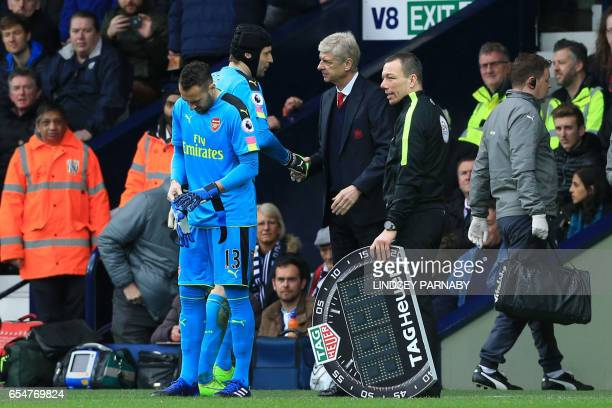 Arsenal's French manager Arsene Wenger shakes hands with Arsenal's Czech goalkeeper Petr Cech as he is substituted during the English Premier League...
