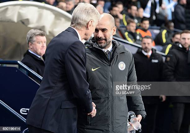 Arsenal's French manager Arsene Wenger shakes hands with Manchester City's Spanish manager Pep Guardiola as he arrives on the pitch ahead of the...