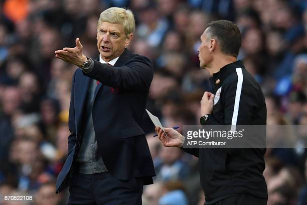 Arsenal's French manager Arsene Wenger speaks to fourth official Andre Marriner after they concede their third goal during the English Premier League...
