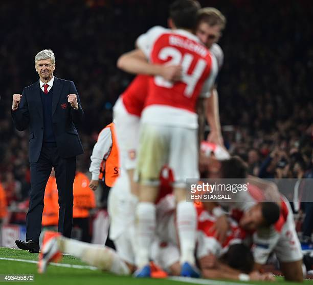 Arsenal's French manager Arsene Wenger watches as his players celebrate Arsenal's German midfielder Mesut Ozil's goal during the UEFA Champions...