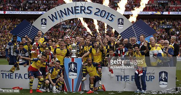 Arsenal's French manager Arsene Wenger watches as his team celebrate with the trophy after winning the FA Cup final football match between Aston...