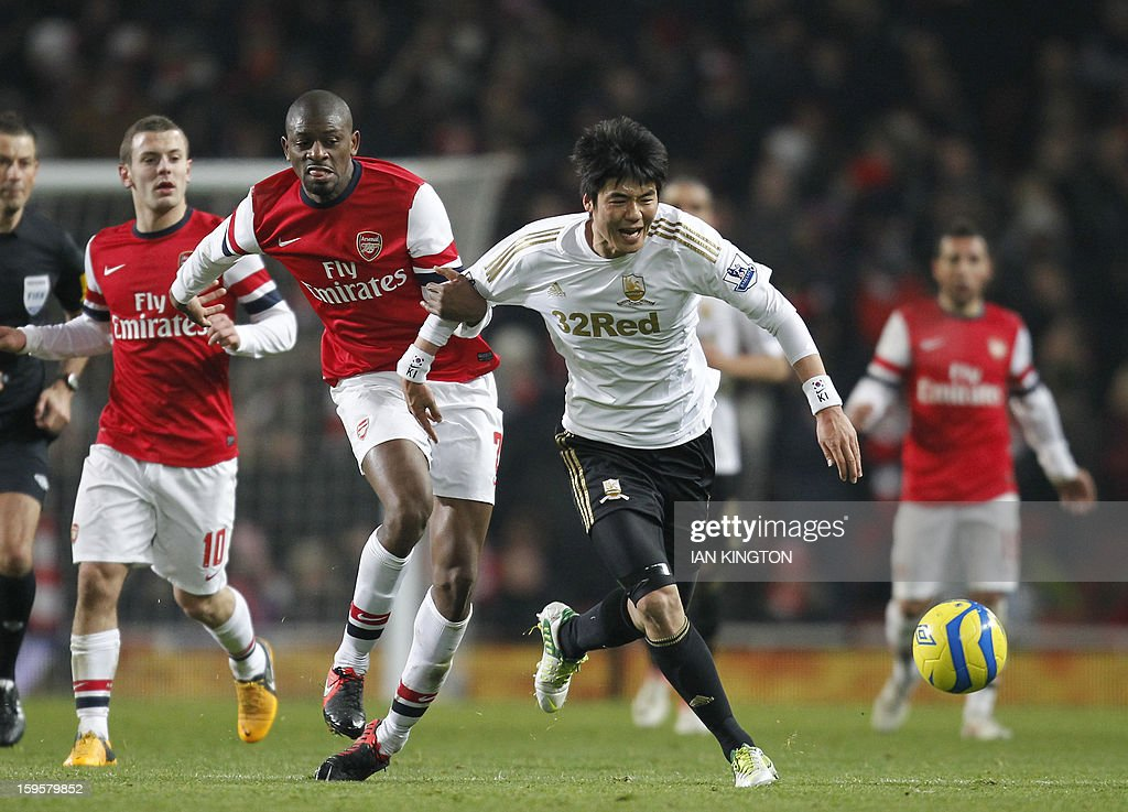 Arsenal's French midfielder Abou Diaby (L) vies with Swansea City's South Korean midfielder Ki Sung-Yueng (R) during the English FA Cup third round replay football match between Arsenal and Swansea City at the Emirates Stadium in London on January 16, 2013. Arsenal won the game 1-0. USE. No use with unauthorized audio, video, data, fixture lists, club/league logos or 'live' services. Online in-match use limited to 45 images, no video emulation. No use in betting, games or single club/league/player publications.