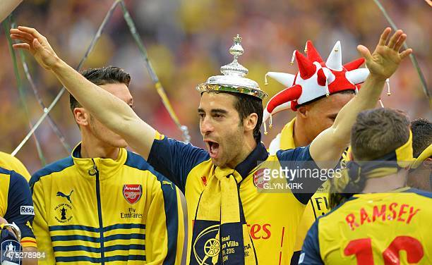 Arsenal's French midfielder Mathieu Flamini poses with the trophy after winning the FA Cup final football match between Aston Villa and Arsenal at...
