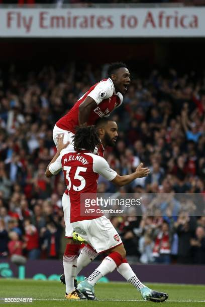 Arsenal's French striker Alexandre Lacazette celebrates with Arsenal's Egyptian midfielder Mohamed Elneny and Arsenal's English striker Danny Welbeck...