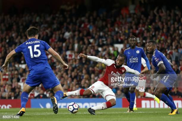 Arsenal's French striker Alexandre Lacazette has an unsuccessful shot as Leicester City's English defender Harry Maguire Leicester City's Nigerian...