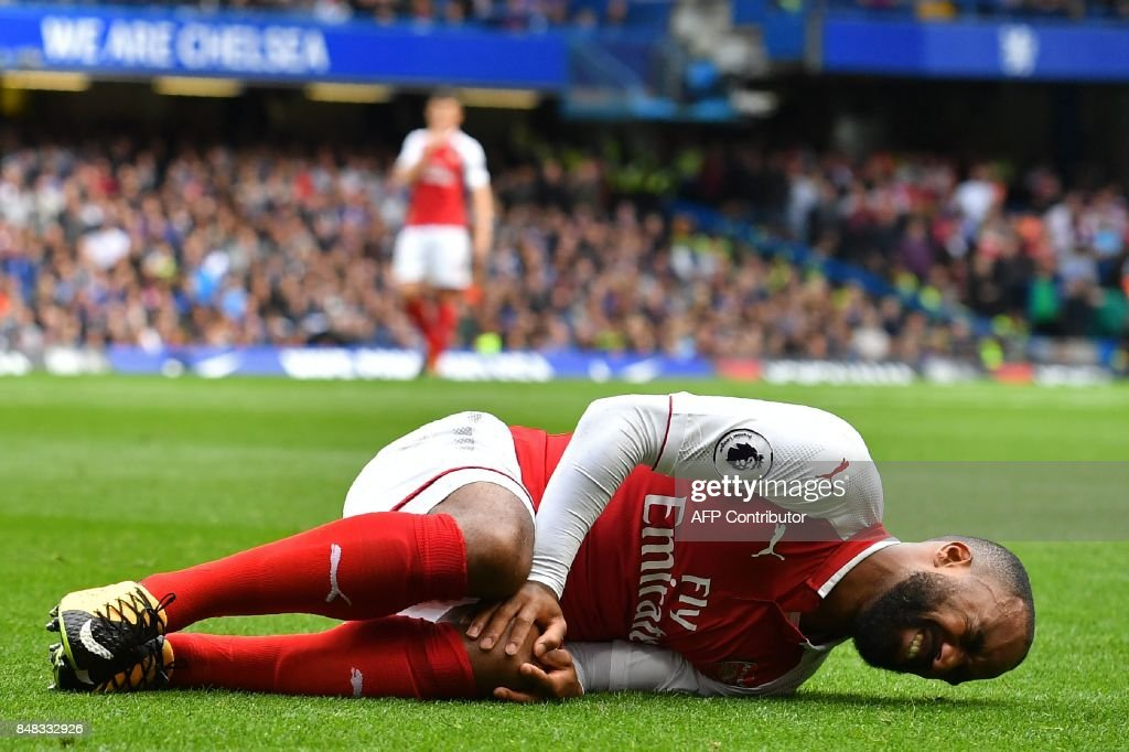 TOPSHOT - Arsenal's French striker Alexandre Lacazette lies injured after a collision with Chelsea's Nigerian midfielder Victor Moses (not pictured) during the English Premier League football match between Chelsea and Arsenal at Stamford Bridge in London on September 17, 2017. / AFP PHOTO / Ben STANSALL / RESTRICTED TO EDITORIAL USE. No use with unauthorized audio, video, data, fixture lists, club/league logos or 'live' services. Online in-match use limited to 75 images, no video emulation. No use in betting, games or single club/league/player publications. /