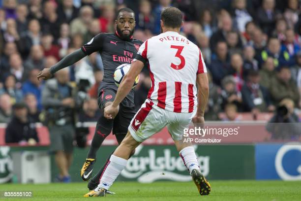 Arsenal's French striker Alexandre Lacazette vies with Stoke City's Dutch defender Erik Pieters during the English Premier League football match...