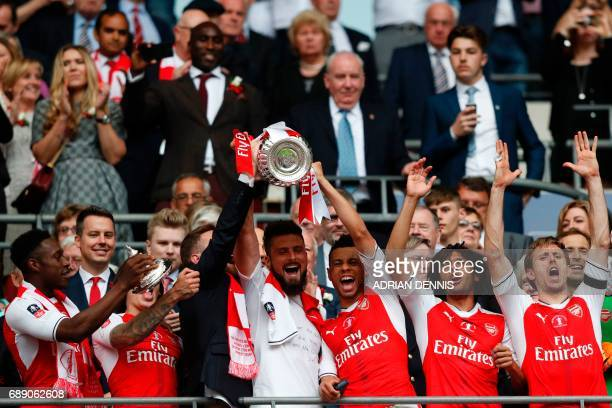 Arsenal's French striker Olivier Giroud and Arsenal's French midfielder Francis Coquelin lift up the FA Cup trophy as Arsenal players celebrate their...