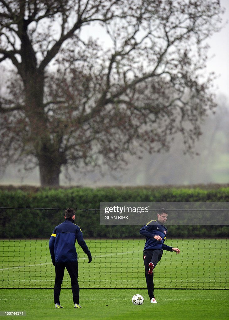 Arsenal's French striker Olivier Giroud (R) and French defender Laurent Koscielny (L) attend a training session at Arsenal's training facility in London Colney in Hertfordshire north of London on November 20, 2012 on the eve of their UEFA Champions League group B football match against Montpellier. AFP PHOTO / GLYN KIRK