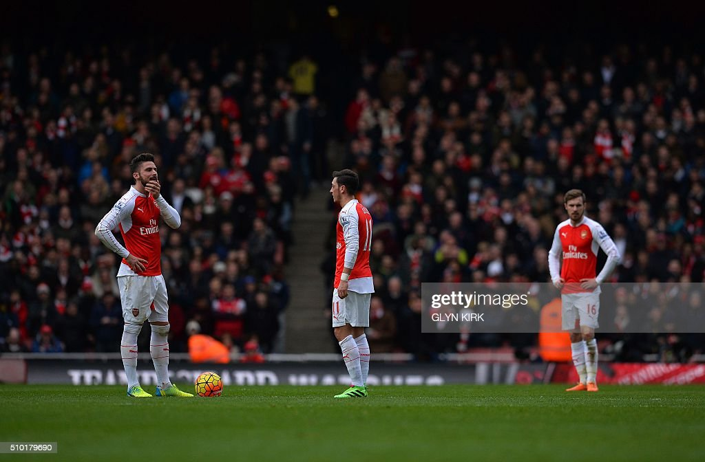 Arsenal's French striker Olivier Giroud (L), Arsenal's German midfielder Mesut Ozil (C) and Arsenal's Welsh midfielder Aaron Ramsey react during the English Premier League football match between Arsenal and Leicester at the Emirates Stadium in London on February 14, 2016. / AFP / GLYN KIRK / RESTRICTED TO EDITORIAL USE. No use with unauthorized audio, video, data, fixture lists, club/league logos or 'live' services. Online in-match use limited to 75 images, no video emulation. No use in betting, games or single club/league/player publications. /