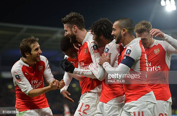 Arsenal's French striker Olivier Giroud celebrates with teammates after scoring the opening goal of the English FA cup fifth round replay football...