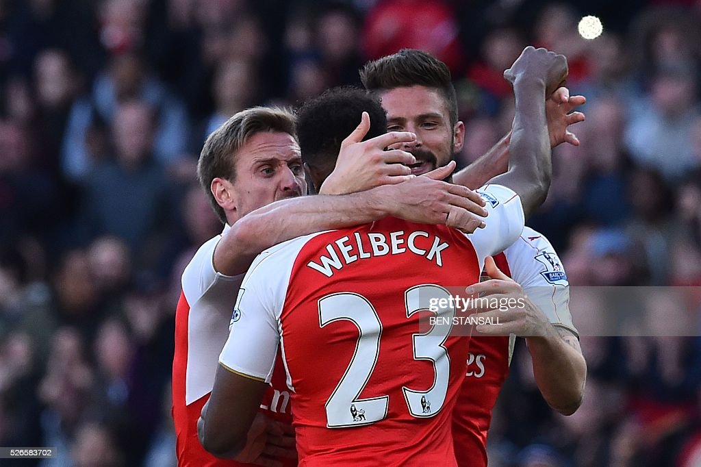 Arsenal's French striker Olivier Giroud (R) congratulates Arsenal's English striker Danny Welbeck (C) after Arsenal's English striker Danny Welbeck scored the opening goal during the English Premier League football match between Arsenal and Norwich at the Emirates Stadium in London on April 30, 2016. / AFP / BEN STANSALL / RESTRICTED TO EDITORIAL USE. No use with unauthorized audio, video, data, fixture lists, club/league logos or 'live' services. Online in-match use limited to 75 images, no video emulation. No use in betting, games or single club/league/player publications. /