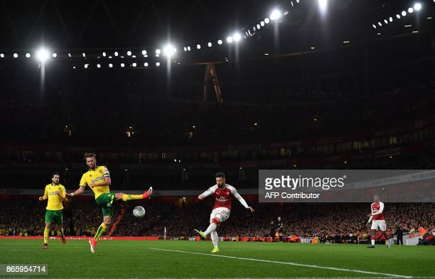 TOPSHOT Arsenal's French striker Olivier Giroud crosses the ball past Norwich City's Portuguese defender Ivo Pinto during the English League Cup...