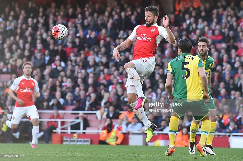 Arsenal's French striker Olivier Giroud (C) heads the ball down to set up the opening goal for Arsenal's English striker Danny Welbeck during the English Premier League football match between Arsenal and Norwich at the Emirates Stadium in London on April 30, 2016. / AFP / BEN STANSALL / RESTRICTED TO EDITORIAL USE. No use with unauthorized audio, video, data, fixture lists, club/league logos or 'live' services. Online in-match use limited to 75 images, no video emulation. No use in betting, games or single club/league/player publications. /