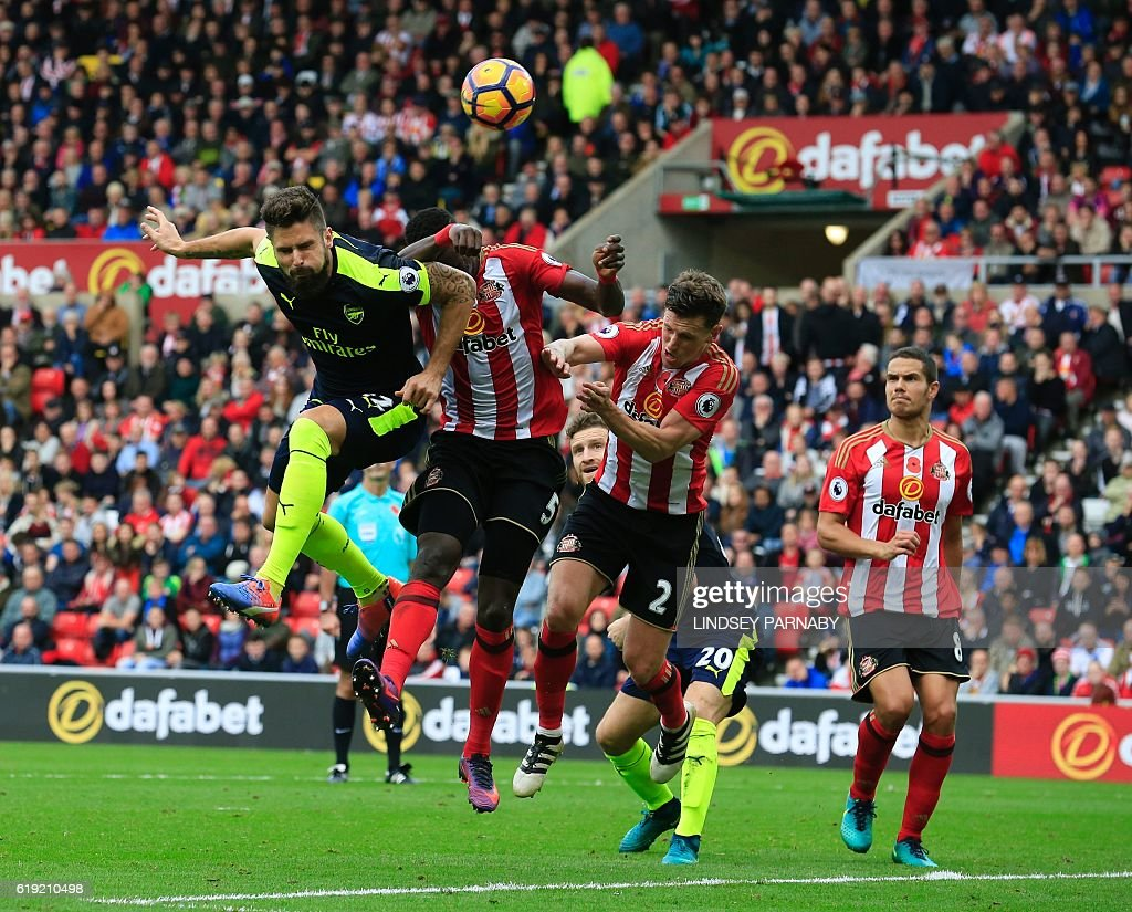 Arsenal's French striker Olivier Giroud heads the ball to score their third goal during the English Premier League football match between Sunderland and Arsenal at the Stadium of Light in Sunderland, northeast England on October 29, 2016. / AFP / Lindsey PARNABY / RESTRICTED TO EDITORIAL USE. No use with unauthorized audio, video, data, fixture lists, club/league logos or 'live' services. Online in-match use limited to 75 images, no video emulation. No use in betting, games or single club/league/player publications. /