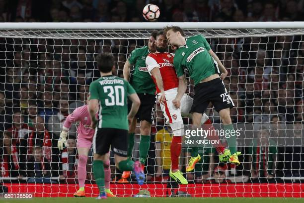 Arsenal's French striker Olivier Giroud is hurt in this clash with Lincoln City's English defender Luke Waterfall and Lincoln City's English defender...