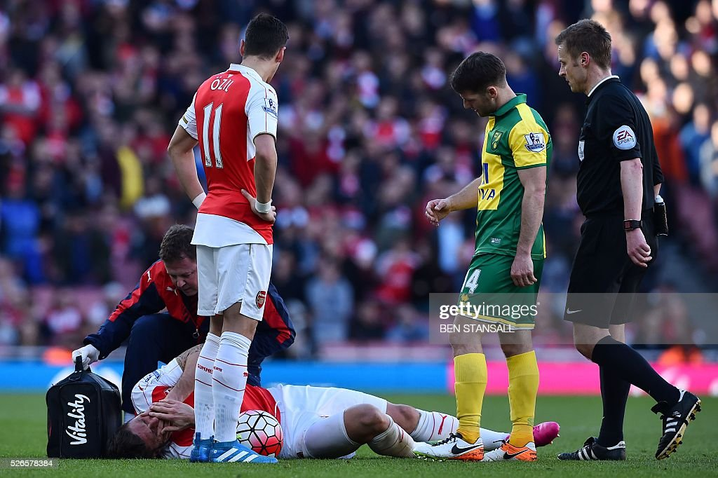 Arsenal's French striker Olivier Giroud (L floor) lies on the pitch and receives treatement after clashing with Norwich City's Cameroonian defender Sebastien Bassong as they contested a header during the English Premier League football match between Arsenal and Norwich at the Emirates Stadium in London on April 30, 2016. / AFP / BEN STANSALL / RESTRICTED TO EDITORIAL USE. No use with unauthorized audio, video, data, fixture lists, club/league logos or 'live' services. Online in-match use limited to 75 images, no video emulation. No use in betting, games or single club/league/player publications. /