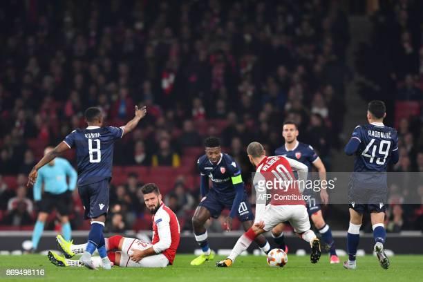 Arsenal's French striker Olivier Giroud nurses an injury as Red Star Belgrade's Dutch midfielder Mitchell Donald vies with Arsenal's English...