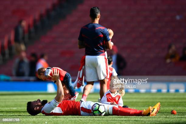 Arsenal's French striker Olivier Giroud plays with son Evan and daughter Jade on the pitch at the end of the English Premier League football match...