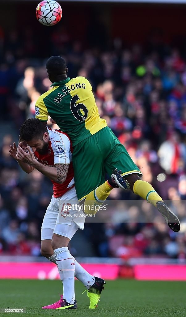 Arsenal's French striker Olivier Giroud (L) reacts as Norwich City's Cameroonian defender Sebastien Bassong (R) climbs above him to meet a header during the English Premier League football match between Arsenal and Norwich at the Emirates Stadium in London on April 30, 2016. / AFP / BEN STANSALL / RESTRICTED TO EDITORIAL USE. No use with unauthorized audio, video, data, fixture lists, club/league logos or 'live' services. Online in-match use limited to 75 images, no video emulation. No use in betting, games or single club/league/player publications. /