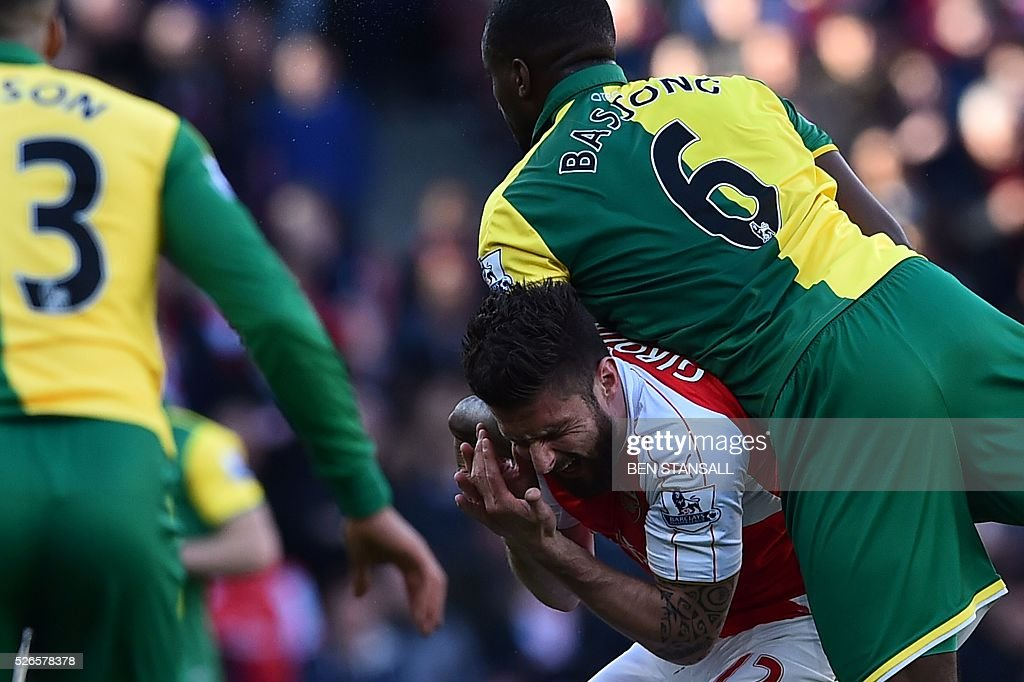 Arsenal's French striker Olivier Giroud (2R) reacts as Norwich City's Cameroonian defender Sebastien Bassong (R) climbs above him to meet a header during the English Premier League football match between Arsenal and Norwich at the Emirates Stadium in London on April 30, 2016. / AFP / BEN STANSALL / RESTRICTED TO EDITORIAL USE. No use with unauthorized audio, video, data, fixture lists, club/league logos or 'live' services. Online in-match use limited to 75 images, no video emulation. No use in betting, games or single club/league/player publications. /