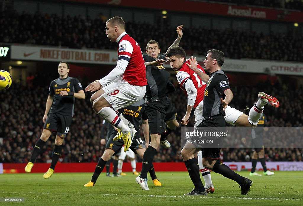 """Arsenal's French striker Olivier Giroud (2R) scores Arsenal's first goal during the English Premier League football match between Arsenal and Liverpool at The Emirates Stadium in north London on January 30, 2013. AFP PHOTO / IAN KINGTON USE. No use with unauthorized audio, video, data, fixture lists, club/league logos or """"live"""" services. Online in-match use limited to 45 images, no video emulation. No use in betting, games or single club/league/player publications."""