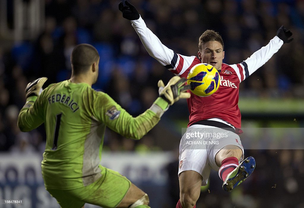"Arsenal's French striker Olivier Giroud (R) shoots at the goal in front of Reading's Australian goalkeeper Adam Federici (L) during the English Premier League football match between Reading and Arsenal at Madejski Stadium in Reading on December 17, 2012. USE. No use with unauthorized audio, video, data, fixture lists, club/league logos or ""live"" services. Online in-match use limited to 45 images, no video emulation. No use in betting, games or single club/league/player publications."