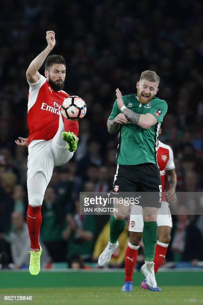Arsenal's French striker Olivier Giroud vies with Lincoln City's Irish midfielder Alan Power during the English FA cup quarter final football match...