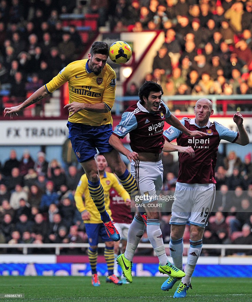 Arsenal's French striker Olivier Giroud (L) vies with West Ham United's English defender James Tomkins (C) and West Ham United's Welsh defender James Collins (R) during the English Premier League football match between West Ham United and Arsenal at the Boleyn Ground, Upton Park, in east London on December 26, 2013. AFP PHOTO / CARL COURT USE. No use with unauthorized audio, video, data, fixture lists, club/league logos or live services. Online in-match use limited to 45 images, no video emulation. No use in betting, games or single club/league/player publications.