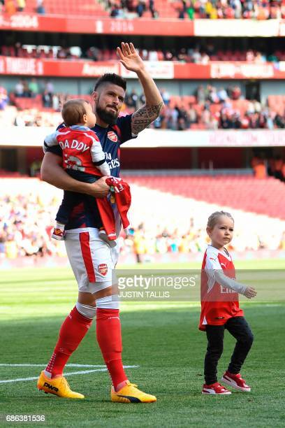 Arsenal's French striker Olivier Giroud walks on the pitch with son Evan and daughter Jade after the English Premier League football match between...