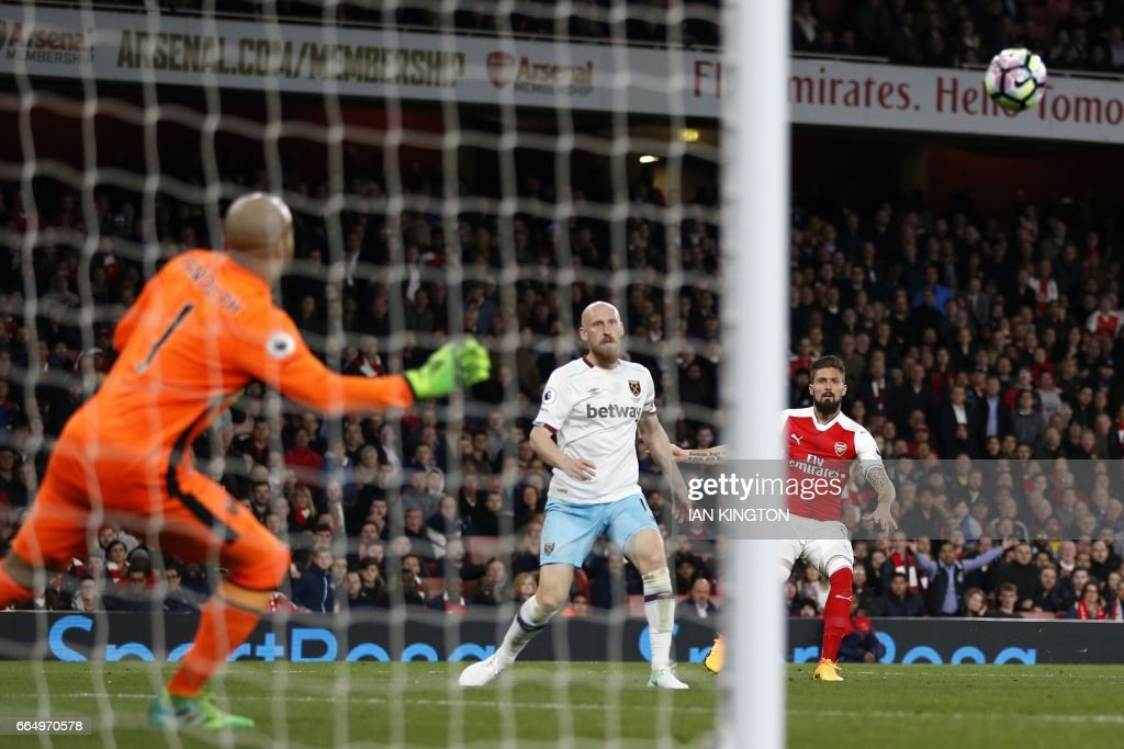 Arsenal's French striker Olivier Giroud (R) watches his shot beat West Ham United's Irish goalkeeper Darren Randolph (L) to make the score 3-0 during the English Premier League football match between Arsenal and West Ham United at the Emirates Stadium in London on April 5, 2017. / AFP PHOTO / Ian KINGTON / RESTRICTED TO EDITORIAL USE. No use with unauthorized audio, video, data, fixture lists, club/league logos or 'live' services. Online in-match use limited to 75 images, no video emulation. No use in betting, games or single club/league/player publications. /