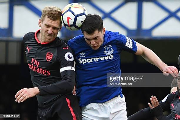 Arsenal's German defender Per Mertesacker and Everton's English defender Michael Keane go for the same high ball during the English Premier League...