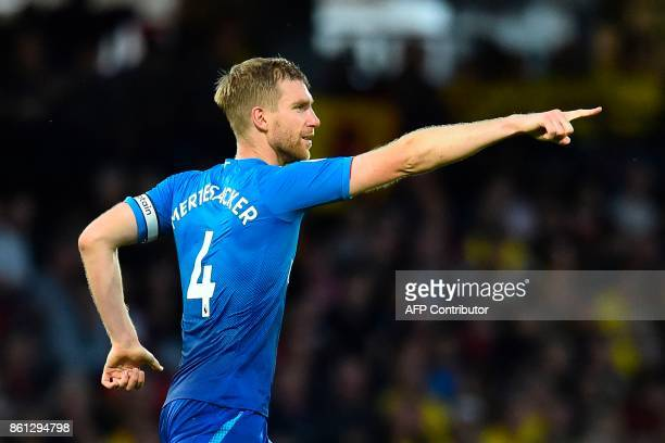 Arsenal's German defender Per Mertesacker celebrates scoring the opening goal during the English Premier League football match between Watford and...