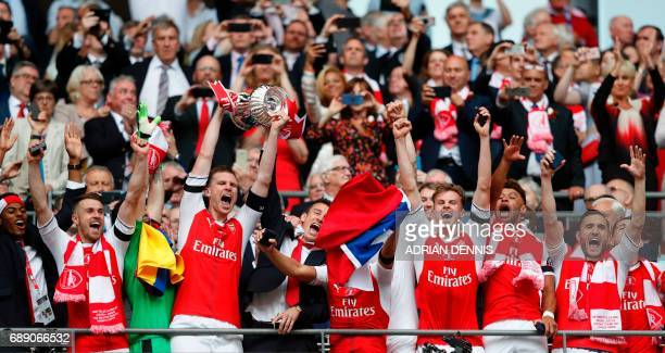 Arsenal's German defender Per Mertesacker lifts the FA Cup trophy as Arsenal players celebrate their victory over Chelsea in the English FA Cup final...