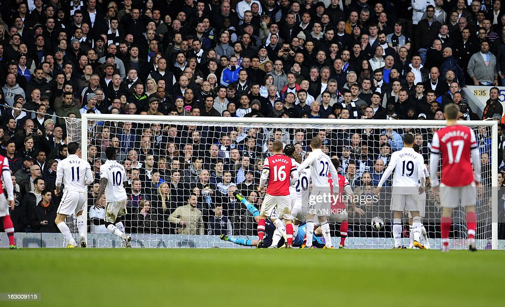 """Arsenal's German defender Per Mertesacker (L out of picture) scores Arsenal's first goal during the English Premier League football match between Tottenham Hotspur and Arsenal at White Hart Lane in north London on March 3, 2013. USE. No use with unauthorized audio, video, data, fixture lists, club/league logos or """"live"""" services. Online in-match use limited to 45 images, no video emulation. No use in betting, games or single club/league/player publications"""