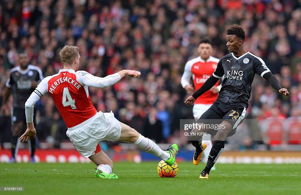 Arsenal's German defender Per Mertesacker (L) vies with Leicester City's English midfielder Demarai Gray during the English Premier League football match between Arsenal and Leicester at the Emirates Stadium in London on February 14, 2016. / AFP / GLYN KIRK / RESTRICTED TO EDITORIAL USE. No use with unauthorized audio, video, data, fixture lists, club/league logos or 'live' services. Online in-match use limited to 75 images, no video emulation. No use in betting, games or single club/league/player publications. /