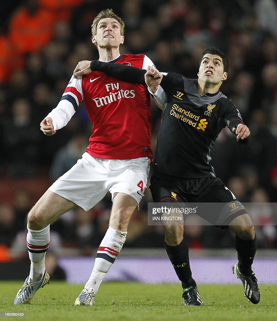 """Arsenal's German defender Per Mertesacker (L) vies with Liverpool's Uruguan striker Luis Suarez (R) during the English Premier League football match between Arsenal and Liverpool at The Emirates Stadium in north London on January 30, 2013. USE. No use with unauthorized audio, video, data, fixture lists, club/league logos or """"live"""" services. Online in-match use limited to 45 images, no video emulation. No use in betting, games or single club/league/player publications."""