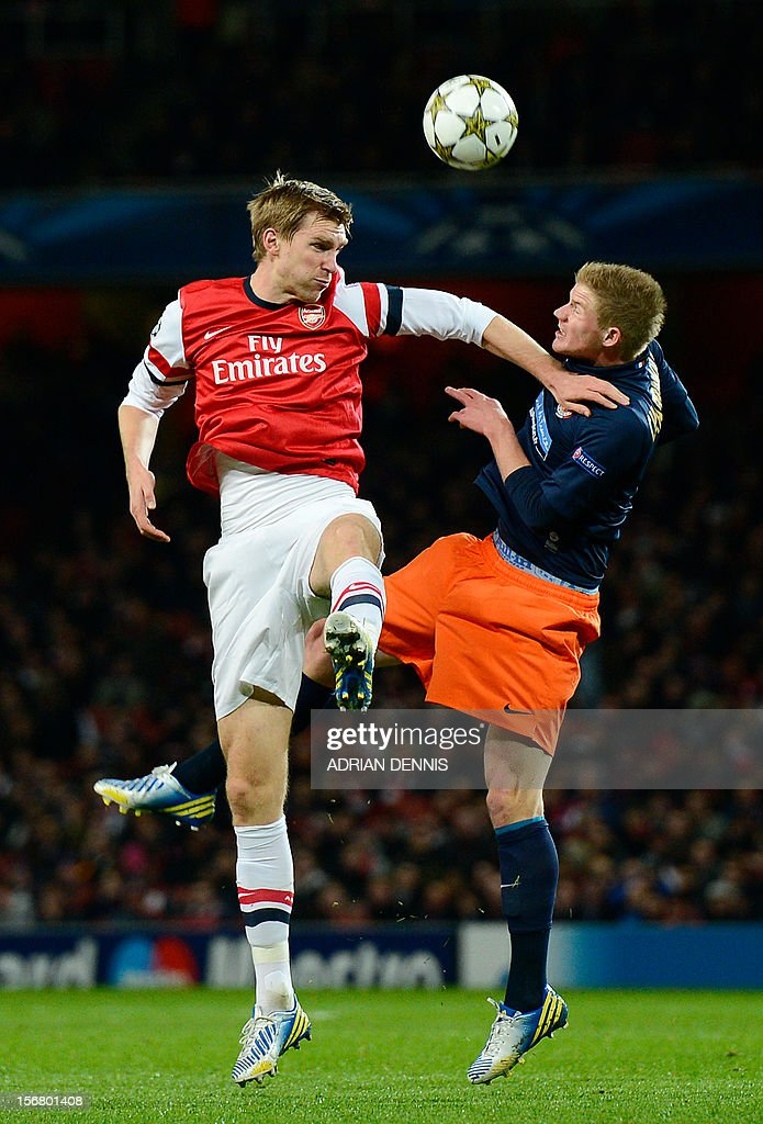 Arsenal's German defender Per Mertesacker (L) vies with Montpellier's French striker Gaetan Charbonnier (R) during the UEFA Champions League group B football match against Montpellier at the Emirates Stadium, North London, on November 21, 2012. AFP PHOTO / ADRIAN DENNIS